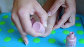 La ragazza dipinge i suoi chiodi sul suo piede destro stock footage