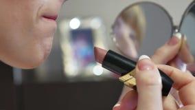 La ragazza dipinge le sue labbra con rossetto dell'interno archivi video