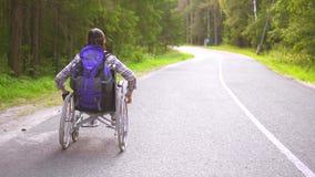 La ragazza disabile in un viaggiatore della sedia a rotelle guida sulla strada principale video d archivio