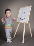 La ragazza disegna con la spazzola sul cavalletto fotografie stock