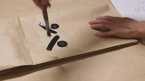 La ragazza disegna con una spazzola sulle varie emozioni dei sacchi di carta Il concetto delle emozioni negli smiley fotografie stock libere da diritti
