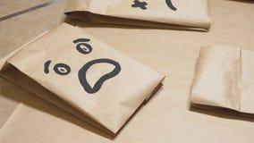 La ragazza disegna con una spazzola sulle varie emozioni dei sacchi di carta Il concetto delle emozioni negli smiley immagine stock