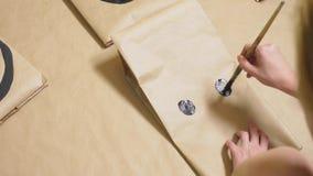 La ragazza disegna con una spazzola sulle varie emozioni dei sacchi di carta Il concetto delle emozioni negli smiley immagine stock libera da diritti