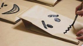 La ragazza disegna con una spazzola sulle varie emozioni dei sacchi di carta Il concetto delle emozioni negli smiley fotografia stock libera da diritti
