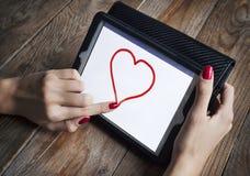 La ragazza disegna il cuore sulla compressa Immagini Stock