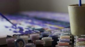 La ragazza disegna un'immagine dai numeri, con le pitture blu acriliche che immergono una spazzola in un bicchiere d'acqua ed in  archivi video