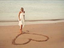 La ragazza dissipa un cuore nella sabbia Fotografie Stock