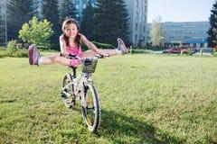 La ragazza divertente allegra in un rosa copre sulla sua bici Immagini Stock Libere da Diritti