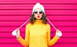 La ragazza divertente che soffia le labbra rosse fa il bacio dell'aria che porta il cappello giallo tricottato variopinto del mag immagine stock