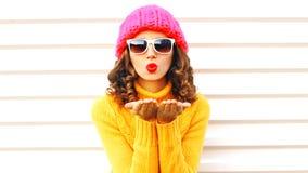 La ragazza divertente che soffia le labbra rosse fa invia il bacio dell'aria che indossa l'ha tricottato variopinto immagine stock