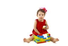 La ragazza divertente del bambino che gioca con la costruzione ha messo sopra bianco Immagine Stock