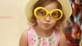La ragazza divertente del bambino in occhiali da sole ed in un cappello sorride Ritratto di un primo piano del bambino stock footage