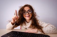 La ragazza divertente del nerd che lavora al computer fotografia stock libera da diritti