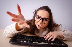 La ragazza divertente del nerd che lavora al computer immagini stock libere da diritti