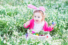 La ragazza divertente in orecchie del coniglietto con le uova in primavera fiorisce Fotografie Stock