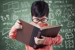 La ragazza dolce impara con il libro vicino alla lavagna Fotografia Stock