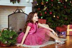 La ragazza dolce in un vestito rosa sorride e si siede vicino al firepl fotografie stock libere da diritti