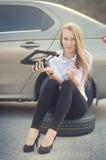 La ragazza domandata Automobile rotta su un fondo La donna si siede su una ruota Riparazione sexy della giovane donna un'automobi Fotografie Stock Libere da Diritti