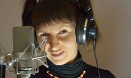 La ragazza, donna in uno studio di registrazione canta una canzone immagini stock
