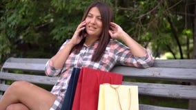 La ragazza dopo la compera si siede nel parco sul banco e nei colloqui sul telefono che discute gli acquisti che hanno un buon um video d archivio