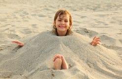 La ragazza dopo nuoto è sepolta in sabbia sulla spiaggia immagini stock