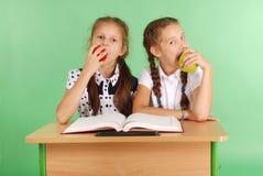 La ragazza due in un uniforme scolastico che si siede allo scrittorio e mangia le mele Fotografia Stock Libera da Diritti