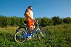 La ragazza e l'uomo con le biciclette si abbracciano Fotografie Stock