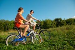 La ragazza e l'uomo vanno per azionamento sulle biciclette in giorno pieno di sole Fotografie Stock