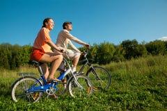 La ragazza e l'uomo vanno per azionamento sulle biciclette in giorno pieno di sole fotografia stock