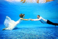 La ragazza e l'uomo in vestiti da sposa nuotano underwater nello stagno per incontrarsi Immagini Stock Libere da Diritti