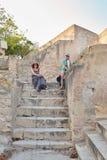 La ragazza e la donna si siedono sulla vecchia scala di pietra gialla di calcare nel castello di Santa Barbara, Alicante, Spagna Fotografie Stock Libere da Diritti