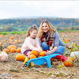 La ragazza e la madre del bambino che si divertono sulla zucca sistemano Fotografia Stock Libera da Diritti