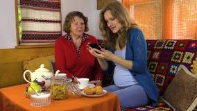 La ragazza e la nonna si siedono alla tavola con tè, foto dell'orologio sul telefono stock footage