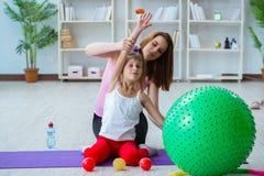 La ragazza e la madre che si esercitano a casa Fotografie Stock