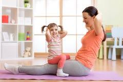 La ragazza e la madre del bambino fanno relativo alla ginnastica sulla stuoia a casa Fotografie Stock Libere da Diritti