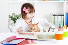 La ragazza e un gatto hanno letto un libro illustrato fotografia stock