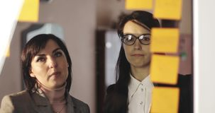 La ragazza ed il mezzo hanno invecchiato la donna di affari che esamina il pianificatore della parete di vetro con le note di Pos video d archivio