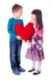 La ragazza ed il ragazzo che tengono un grande cuore rosso hanno modellato il cuscino Immagine Stock