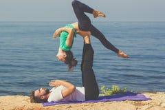La ragazza ed il ragazzo delle coppie stanno praticando il acroyoga sul Fotografia Stock Libera da Diritti
