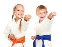 La ragazza ed il ragazzo in un kimono su un fondo bianco battono la mano Fotografia Stock Libera da Diritti