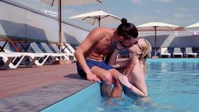 La ragazza ed il tipo che baciano, coppia nel bacio di amore, nuotante nello stagno, femmina emerge dall'acqua, si rilassano nell stock footage