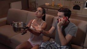 La ragazza ed il tipo si siedono sul sofà Tiene il vaso L'acqua sta colando in  Cerca La ragazza è stupita Il tipo sta parlando s