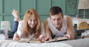 La ragazza ed il tipo stanno leggendo i libri che si situano insieme ad alta voce a letto stock footage