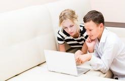 La ragazza ed il tipo stanno sedendo ad un computer portatile Immagine Stock