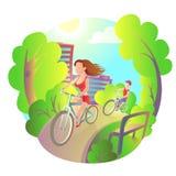 La ragazza ed il tipo su una bici guidano intorno al parco della città Sport all'aperto di attività Viaggio dei ciclisti Fotografia Stock