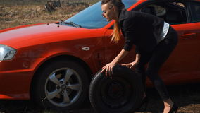 La ragazza elegante rotola la ruota di riserva dell'automobile video d archivio
