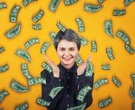 La ragazza emotiva sorride largamente, spande le mani o l'applauso estatico, esclama la felicità mentre i soldi stanno cadendo co immagini stock
