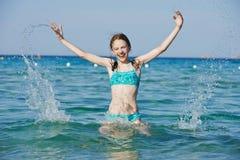 La ragazza emozionante con l'acqua di mare spruzza Immagine Stock