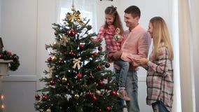 La ragazza emozionante decora l'albero di Natale con le bagattelle archivi video