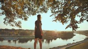 La ragazza entusiasta funziona per incontrare il tramonto sui precedenti della città e solleva le sue mani Video nel moto archivi video